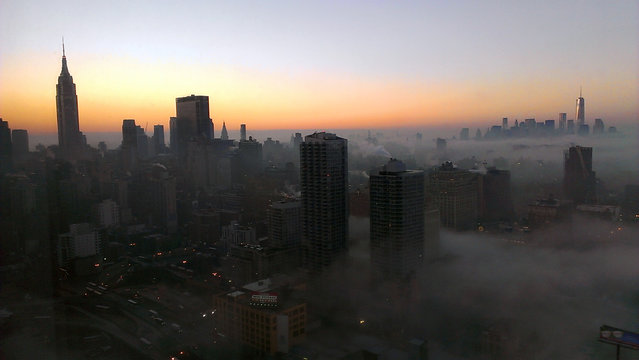 The tower of New York's World Trade Center, right, rises through a blanket of fog on Wednesday morning, Jan. 15, 2014, in this view looking south from the 48th floor at 42nd St. and 11th Ave in Midtown Manhattan. The Empire State Building is visible at left. (Photo by Girish Tewani/AP Photo)