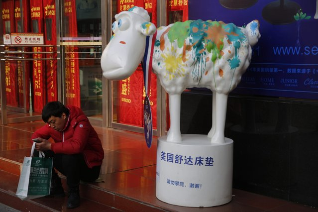 """A Chinese man rests beside a sheep sculpture at a home furnishing market in Beijing city, China, 02 March 2016. US ratings agency Moody's cuts its outlook for China from """"stable"""" to """"negative"""", according to media reports. (Photo by Wu Hong/EPA)"""