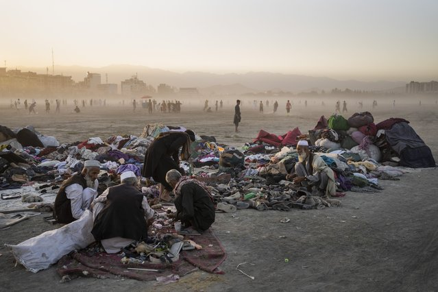 Afghans sort second-hand clothes at the Chaman-e-Hozari Park in Kabul, Afghanistan, Friday, September 17, 2021. (Photo by Bernat Armangue/AP Photo)