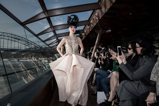 """Fashion show organiser and model Jessica Minh Anh presents one of her creation before her winter fashion show 2017 staged on a floating catwalk aboard a """"bateau-mouche"""" doing an open excursion boat on the Seine river in Paris on January 26, 2017. (Photo by Philippe Lopez/AFP Photo)"""