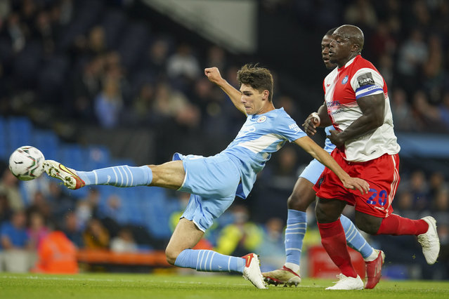 Manchester City's Finlay Burns kicks at the ball as Wycombe Wanderers Adebayo Akinfenwa watches during the English League Cup third round soccer match between Manchester City and Wycombe Wanderers at Etihad Stadium, in Manchester England, Tuesday, September 21, 2021. (Photo by Dave Thompson/AP Photo)