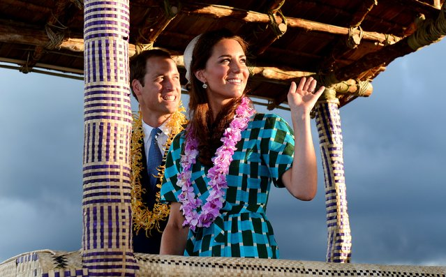 Britain's Prince William (L) and his wife Catherine, the Duchess of Cambridge, wave to the local Solomon Islanders as they leave the airport aboard a truck decorated as canoe in Honiara on September 16, 2012. (Photo by William West/AFP Photo)