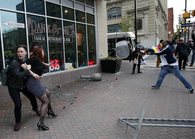 A man, right, throws a chair at a business window as another man tries to restrain a woman attempting to stop the damage, after march to City Hall for Freddie Gray, Saturday, April 25, 2015 in Baltimore. (Photo by Alex Brandon/AP Photo)