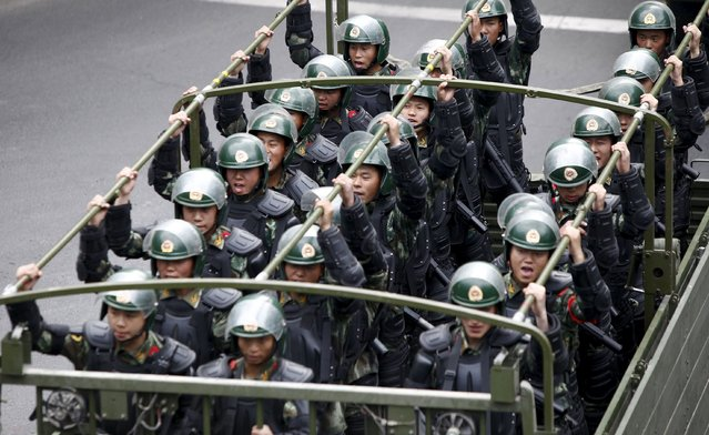 Paramilitary policemen stand on a truck as they travel along a street during an anti-terrorism oath-taking rally in Urumqi, Xinjiang Uighur Autonomous Region, in this May 23, 2014 file picture. (Photo by Reuters/Stringer)