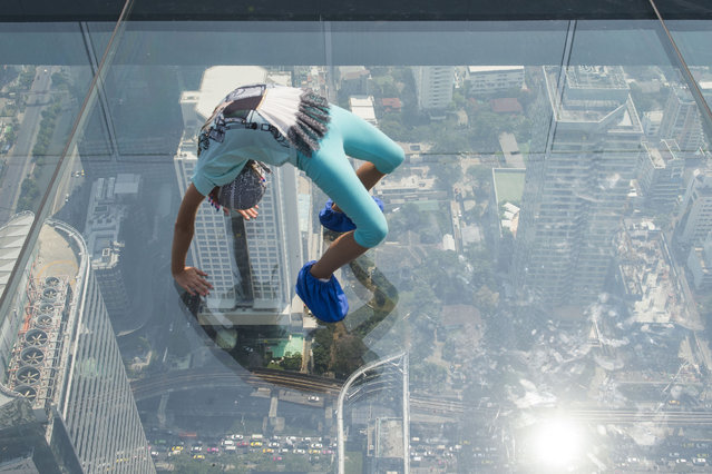 A girl plays on the glass skywalk on the 78th floor of the King Power Mahanakhon skyscraper, Bangkok's highest observation deck, during a polluted day in the city on January 28, 2019. (Photo by Romeo Gacad/AFP Photo)