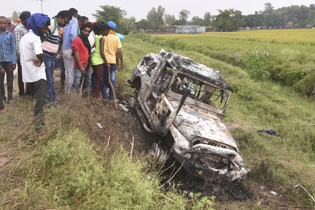 Villagers watch a burnt car which ran over and killed farmers on Sunday, at Tikonia village in Lakhimpur Kheri, Uttar Pradesh state, India, Monday, October 4, 2021. Indian police on Saturday, Oct. 9, arrested the son of a junior minister in Prime Minister Narendra Modi's government as a suspect days after nine people were killed in a deadly escalation of yearlong demonstrations by tens of thousands of farmers against contentious agriculture laws in northern India, a police officer said. (Photo by AP Photo/Stringer)