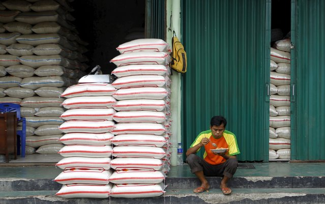 A worker eats his lunch during a break beside sacks of rice at the Cipinang rice market in Jakarta, Indonesia, January 22, 2016. Indonesian agriculture officials routinely inflate rice harvest data to present a rosy picture to the government and keep farm subsidies flowing, but their latest phoney numbers could lead to a severe shortage of the staple in coming months, officials say. (Photo by Garry Lotulung/Reuters)