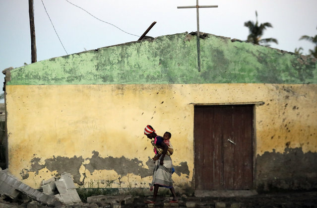 A woman carrying a baby on her back walks over a ruble of damaged houses in Beira, Mozambique, Monday, March 25, 2019. The United Nations is making an emergency appeal for $282 million for the next three months to help Mozambique start recovering from the devastation of Cyclone Idai. (Photo by Themba Hadebe/AP Photo)