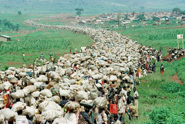 In this December 19, 1996, file photo, tens of thousands of Rwandan refugees, who have been forced by the Tanzanian authorities to return to their country despite fears they will be killed upon their return, stream back towards the Rwandan border on a road in Tanzania. (Photo by Jean-Marc Bouju/AP Photo/File)