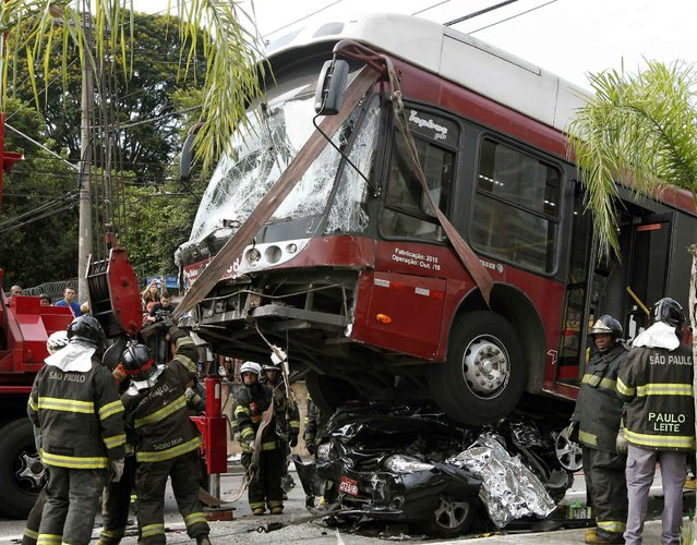 Firefighters work at the site of a bus crash in Sao Paulo February 12, 2014. Two people died and eight were injured in the accident on Wednesday when the bus lost control and crashed into a passenger car. (Photo by Paulo Whitaker/Reuters)