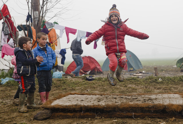 Migrant children play jumping on a muddy mattress at the northern Greek border point of Idomeni, Greece, Friday, March 18, 2016. Leaders of the EU's 28 divided nations plan to reconvene in Brussels this week in hopes of ironing out disagreements on a proposed agreement with Turkey in the migrants crisis. (Photo by Vadim Ghirda/AP Photo)
