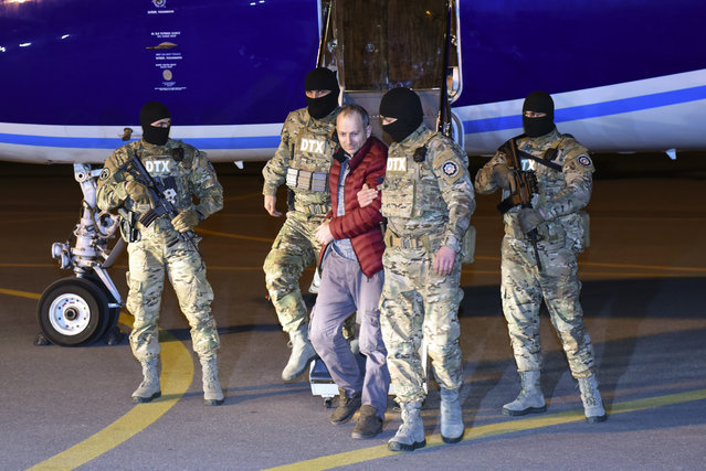 In this Tuesday, February 7, 2017, photo, Alexander Lapshin, center, a Russian blogger who was detained by police in Belarus in December 2016, is escorted out of a plane at the airport by law enforcement agents in Baku, Azerbaijan. The Russian blogger extradited by Belarus has been flown to Azerbaijan, where he faces charges related to his trip to a disputed ethnic Armenian region of the country. (Photo by AP Photo)