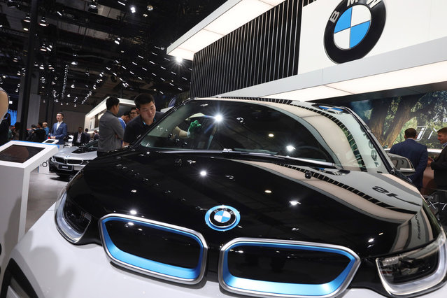 A worker cleans an electric vehicle at the BMW booth during the Auto Shanghai 2019 show in Shanghai Wednesday, April 17, 2019. Automakers are showcasing electric SUVs and sedans with more driving range and luxury features at the Shanghai auto show, trying to appeal to Chinese buyers in their biggest market as Beijing slashes subsidies that have propelled demand. (Photo by Ng Han Guan/AP Photo)