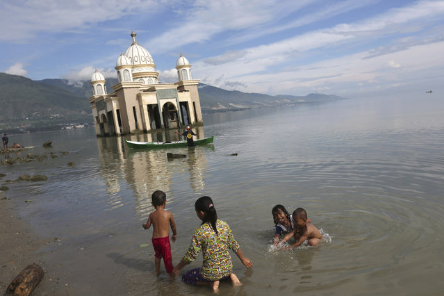 In this Wednesday, April 3, 2019, photo, children play in the water on a beach as a mosque collapsed during the Sept. 28, 2018, earthquake is seen in the background in Palu, Central Sulawesi, Indonesia. The earthquake spawned a large localized tsunami that wiped out coastal areas, while liquefaction caused by the shaking turned entire neighborhoods into rivers of sludge. The disaster killed thousands of people, making it the world's deadliest seismic event in 2018. (Photo by Tatan Syuflana/AP Photo)