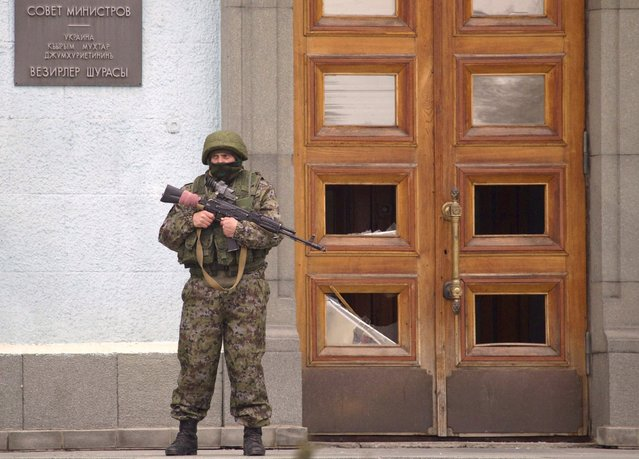 An unidentified man guards the entrance to a local government building in  Simferopol, Ukraine, on Saturday, March 1, 2014. (Photo by Ivan Sekretarev/AP Photo)