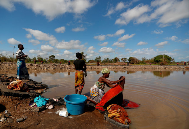 """Maria Jofresse, 25, speaks with her neighbors as they wash clothes in flood water in the aftermath of Cyclone Idai, next to the village of Cheia, which means """"Flood"""" in Portuguese, near Beira, Mozambique, April 2, 2019. (Photo by Zohra Bensemra/Reuters)"""