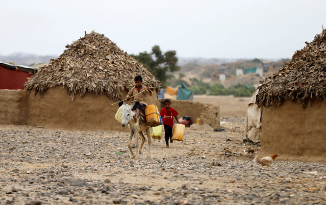 A boy walks behind a donkey used by another boy to transport water jerrycans in an improvised camp for internally displaced people near Abs of the northwestern province of Hajja, Yemen February 18, 2019. Picture taken February 18, 2019. (Photo by Khaled Abdullah/Reuters)