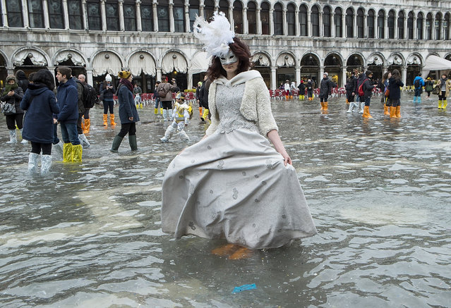 A woman wearing a carnival costume poses in flooded Saint Mark's Square on the last day of Carnival on March 4, 2014 in Venice, Italy. It is the last day of the 2014 Carnival of Venice which has run from February 15 and includes a program of gala dinners, parades, dances, masked balls and music events. High water has been forecast for the final day with the chance of possible flooding. (Photo by Marco Secchi/Getty Images)