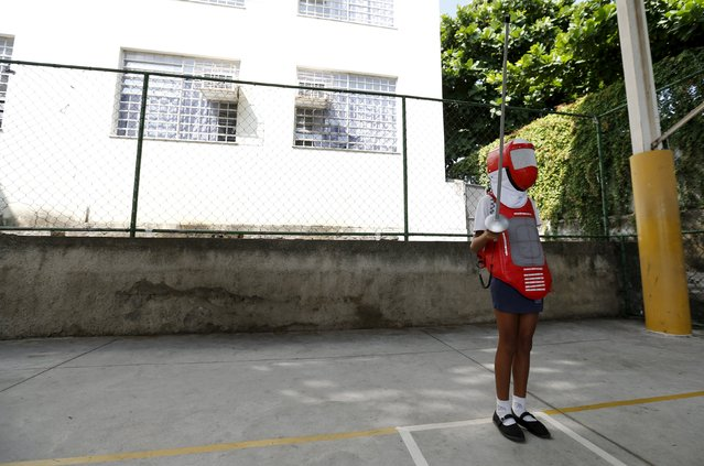 """A child from municipal school Parana poses during the project """"Fencing School"""" in Rio de Janeiro, Brazil, March 30, 2016. Children in Rio de Janeiro lift their sights and their swords to new idols, as a round of fencing workshops takes to public schools. The International Fencing Federation, together with the Brazilian and state federations, will reach 40 public schools in March and April. (Photo by Sergio Moraes/Reuters)"""
