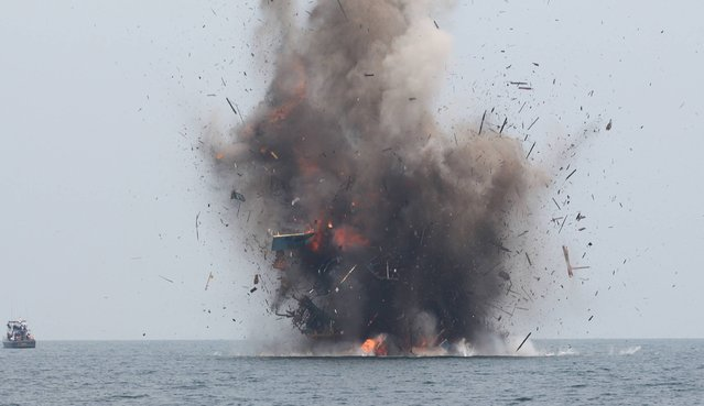 An illegal fishing boat is blown up with explosives by Indonesian authorities in Kuala Langsa, Aceh province on April 5, 2016. Indonesia sank 28 illegal fishing boats from Malaysia, Vietnam and the Philippines on April 5 as the world's largest archipelago nation stepped up a campaign against illegal fishing in its waters. (Photo by AFP Photo/Januar)