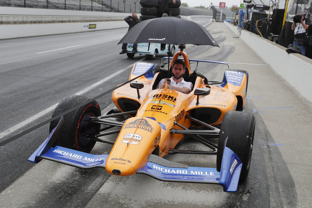The crew of Fernando Alonso, of Spain, pulls the car back to the garage area after rain ended a practice session for the Indianapolis 500 IndyCar auto race at Indianapolis Motor Speedway, Sunday, May 19, 2019 in Indianapolis. (Photo by Michael Conroy/AP Photo)