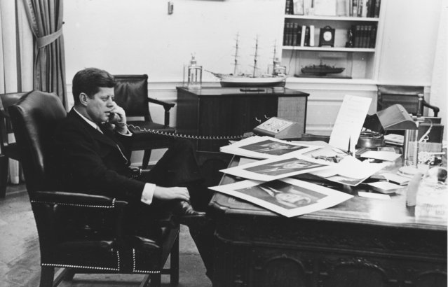 President John F. Kennedy is shown as he ends his official day after 7:30 pm with a final phone call to his press secretary from his Oval Office desk at the White House in Washington, D.C., March 16, 1961.  Spread on the desk are copies of his newly designated  official portrait which he autographed. John Fitzgerald Kennedy was the 35th U.S. President serving from 1961 until his assassination in 1963.  (Photo by Henry Burroughs/AP Photo)