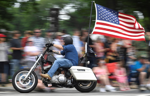 """A motorcycle rider with American flag fluttering passes crowds during the 32nd Annual, and possibly final, Rolling Thunder """"Ride for Freedom"""" during Memorial Day weekend to support veterans and call attention to POWs and MIAs, in Washington, U.S., May 26, 2019. (Photo by Mike Theiler/Reuters)"""