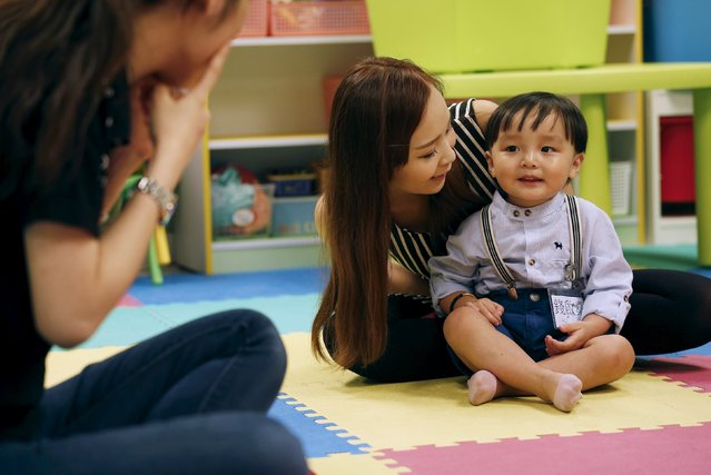 """Two-year-and-three-month-old Carlson Chuen reacts to a teacher beside his mother Rose Cheung during a specialized class preparing toddlers for kindergarten interviews in Hong Kong, China May 17, 2015. Carlson's mother said her son would have to work extra hard because he was born in the year of the Dragon in the Chinese zodiac, an auspicious year that tends to drive couples to have """"dragon babies"""". (Photo by Bobby Yip/Reuters)"""
