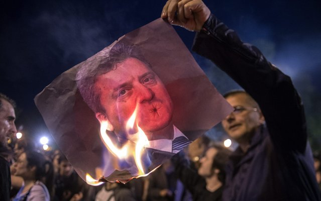 Protesters burn the picture of Macedonian President George Ivanov during the protest against Macedonian President Gjorge Ivanov's decision on wiretapping amnesty, in Skopje, Macedonia, 13 April 2016. Ivanov decided to abolish all judicial cases related to the big wire-tapping scandal that brought the country to early general elections scheduled for 05 June. (Photo by Nake Batev/EPA)