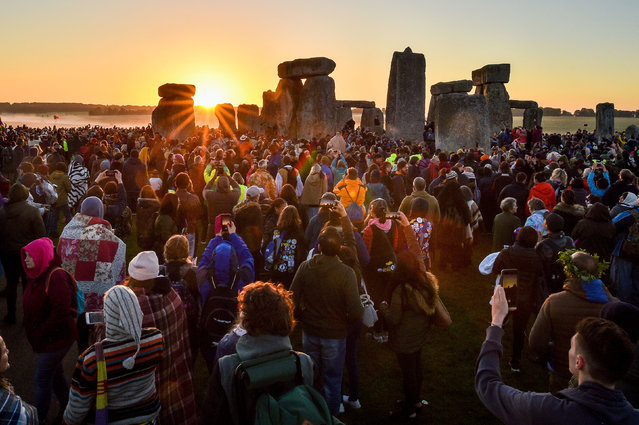Visitors celebrate summer solstice and the dawn of the longest day of the year at Stonehenge on June 21, 2019 in Amesbury, England. Visitors and modern day druids gather at the 5,000 year old stone circle in Wiltshire to see the sunrise on the Summer Solstice dawn in a tradition dating back thousands of years. The solstice sunrise marks the start of the longest day of the year in the Northern Hemisphere. (Photo by Ben Birchall/PA Wire Press Association)