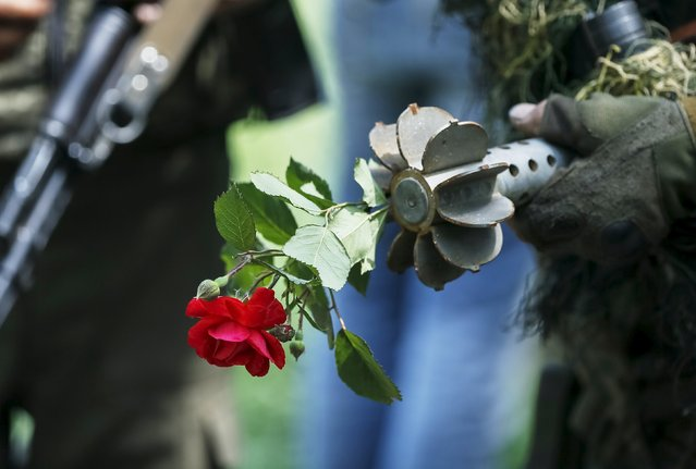 """A Ukrainian serviceman holds a mortar round together with a rose at his position in the town of Maryinka, eastern Ukraine, June 5, 2015. Ukraine's president told his military on Thursday to prepare for a possible """"full-scale invasion"""" by Russia all along their joint border, a day after the worst fighting with Russian-backed separatists in months.  REUTERS/Gleb Garanich"""