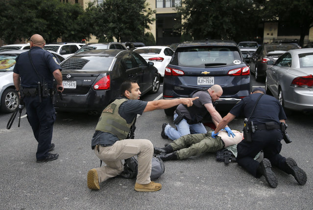 Law enforcement officers attend to an injured shooter in a parking lot after he fired shots at the Earle Cabell Federal Building in downtown Dallas, Monday, June 17, 2019. (Photo by Tom Fox/The Dallas Morning News)