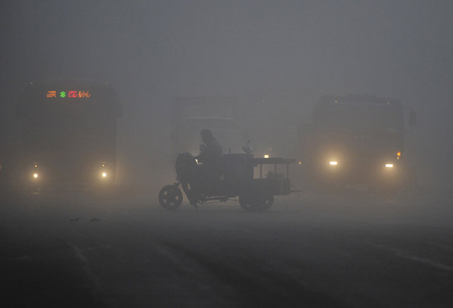 A tricycle travels past a crossroad on a hazy day in Hefei, Anhui province March 30, 2014. China's plan for a market in air pollution permits promises to help clean up its air cheaply, but the move could prove just as useless as previous environmental policies unless the government stamps out lax enforcement and spotty data. (Photo by Reuters/Stringer)