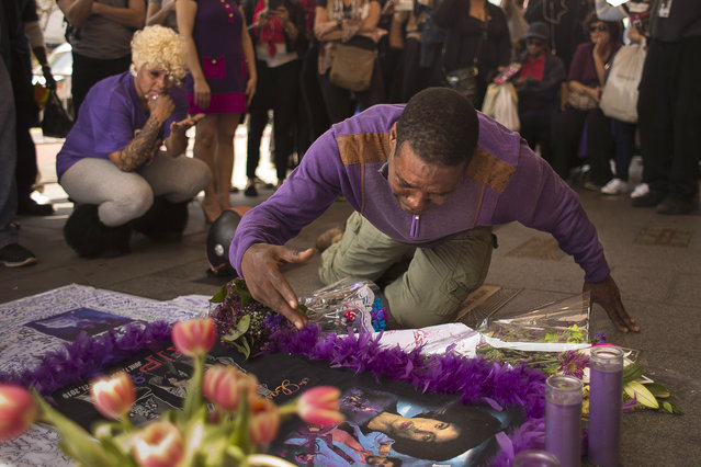 A fan cries at a makeshift memorial created in remembrance of singer Prince outside Apollo Theatre in New York , Friday, April 22, 2016. The pop star died Thursday at the age of 57. (Photo by Andres Kudacki/AP Photo)