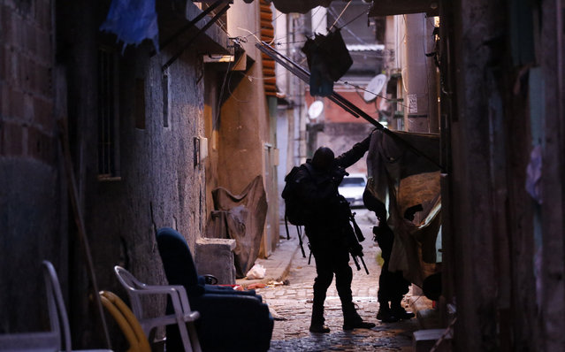 A policeman of Special Operations Battalion (BOPE) looks for drugs and weapons at the Mare slums complex in Rio de Janeiro March 30, 2014. (Photo by Ricardo Moraes/Reuters)