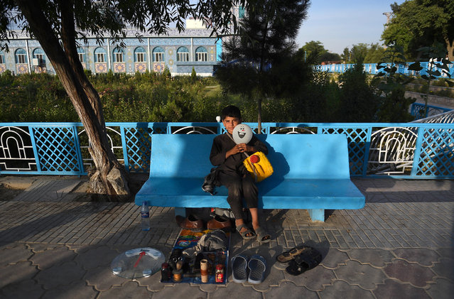 In this photo taken on June 9, 2019, Afghan shoe shiner Qadir, 12, waits for customers along a street in Mazar-i-Sharif. (Photo by Farshad Usyan/AFP Photo)