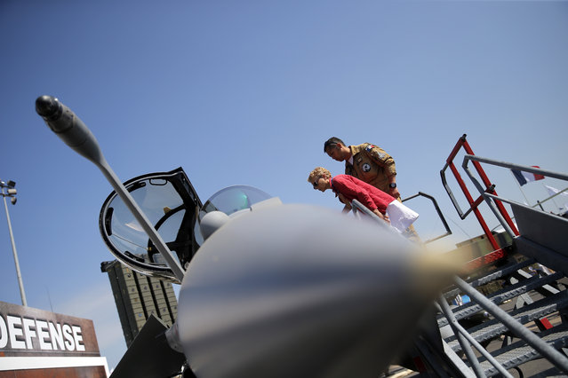 A pilots shows to visitor a Rafale jet fighter during the Paris Air Show, at Le Bourget airport, north of Paris, Wednesday, June 17, 2015. Some 300,000 aviation professionals and spectators are expected at this week's Paris Air Show, coming from around the world to make business deals and see dramatic displays of aeronautic prowess and the latest air and space technology. (AP Photo/Christophe Ena)