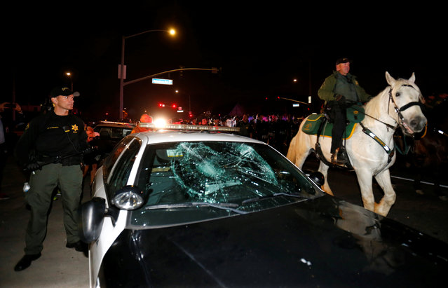 Police on horseback and in riot gear pass by a damaged police car as they break up a demonstration outside Republican U.S. presidential candidate Donald Trump's campaign rally in Costa Mesa, California, April 28, 2016. (Photo by Mike Blake/Reuters)