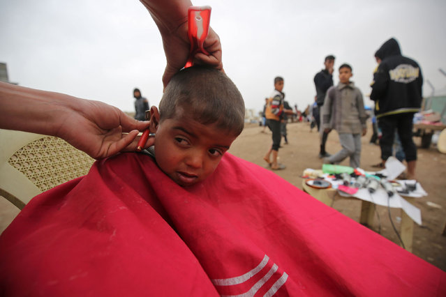A displaced Iraqi boy has a hair cut at the Hamam al- Alil camp, where many residents from Mosul are taking shelter, as the government forces continue their offensive to retake the embattled city from Islamic State (IS) group fighters on March 18, 2017 Iraq began an operation on February 19 to retake west Mosul, which is the last major Islamic State group urban bastion in the country and includes the Old City. (Photo by Ahmad Al-Rubaye/AFP Photo)