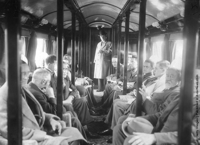 1930: Passengers on the Bennie Railplane in Glasgow; the inventor George Bennie stands at the end of the carriage. The streamlined cars are self propelled, driven by air screws in front and behind, and hang from a steel girder