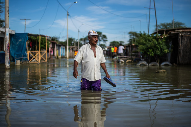 """A local resident wades through water on a street in the """"El Indio"""" settlement on the outskirts of Piura, in northern Peru, on March 23, 2017. The El Nino climate phenomenon is causing muddy rivers to overflow along the entire Peruvian coast, isolating communities and neighbourhoods. (Photo by Ernesto Benavides/AFP Photo)"""