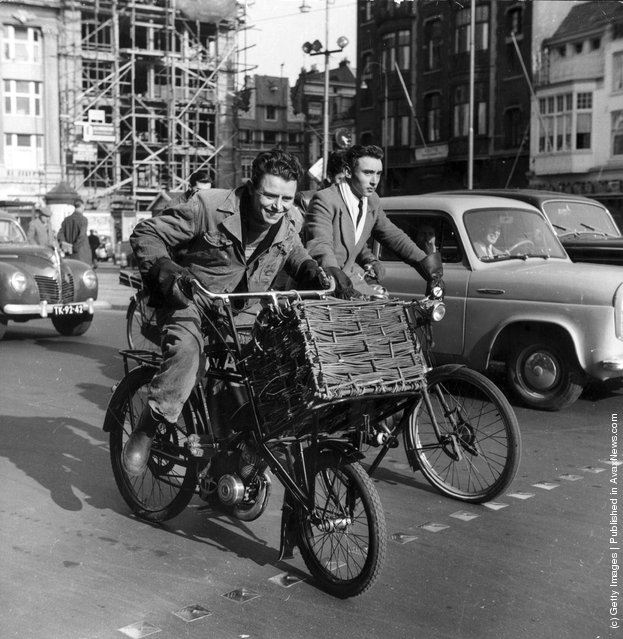 1955: Two young men cycling amongst traffic in Holland, one on a bicycle with a motor attached and a large basket at the front