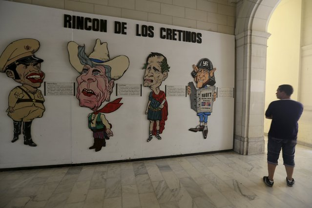 """A man looks a display entitled, """"Corner of the Cretins"""" in reference to (L to R) Cuban dictator Fulgencio Batista, former U.S. Presidents Ronald Reagan, George Bush Sr. and George W. Bush, at the Museum of the Revolution in Havana July 1, 2015. (Photo by Enrique de la Osa/Reuters)"""