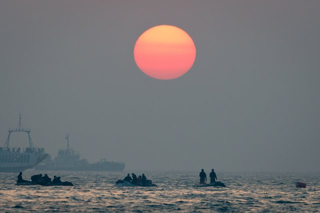 "The sun sets behind search and rescue teams during recovery operations at the site of the ""Suwol"" ferry of the coast of the South Korean island on Jindo on April 22, 2014. Divers began to locate bodies on April 19 inside a submerged South Korean ferry as the detained captain defended his decision to delay evacuation of the ship when it capsized nearly four days ago with 476 people on board. (Photo by Ed Jones/AFP Photo)"