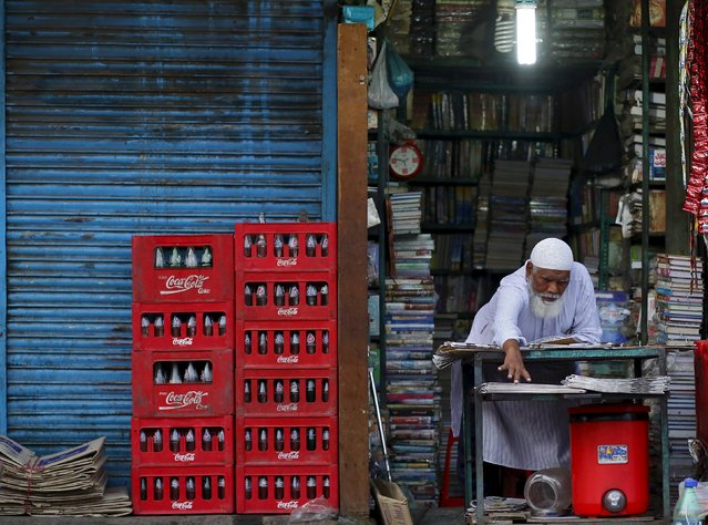 A shopkeeper extends his hand as he arranges newspapers for sale at his shop during early morning in the old quarters of Delhi, India, July 2, 2015. (Photo by Anindito Mukherjee/Reuters)