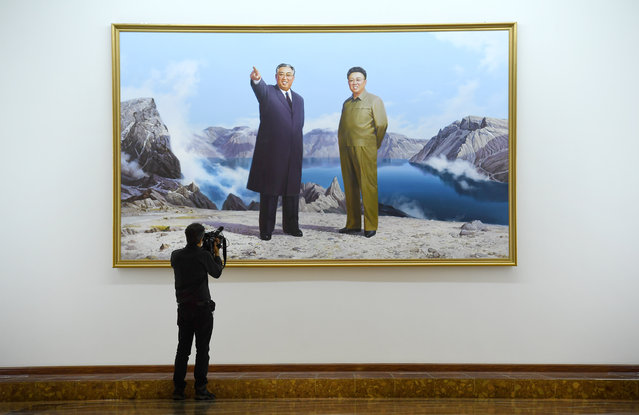 Foreign media films a large portrait of Kim Il Sung and his son Kim Jong Il hung in the lobby of an upscale hotel in Pyongyang, North Korea on May 4, 2016. (Photo by Linda Davidson/The Washington Post)