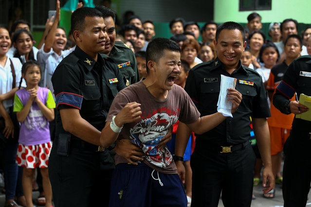 A young man (C) reacts after being exempted from military service during an army draft held at a school in Klong Toey, the dockside slum area in Bangkok, Thailand, April 5, 2017. (Photo by Athit Perawongmetha/Reuters)