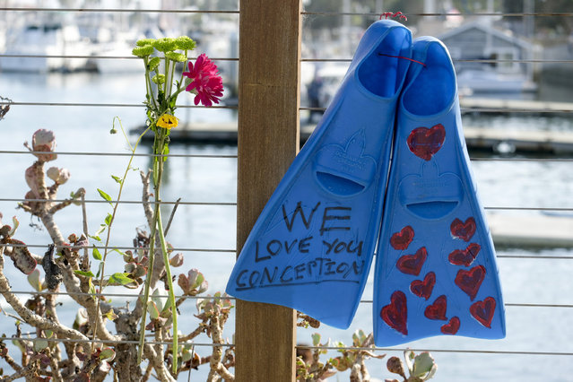 A pair of fins and flowers are placed on the outside of the Sea Landing at Santa Barbara Harbor in Santa Barbara, Calif., Monday, September 2, 2019. A fire raged through a boat carrying recreational scuba divers anchored near an island off the Southern California coast early Monday, leaving multiple people dead and hope diminishing that any of the more than two dozen people still missing would be found alive. (Photo by Ringo H.W. Chiu/AP Photo)