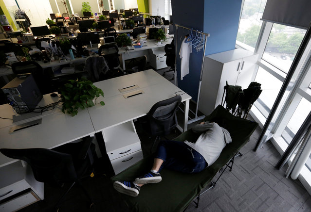 Kou Meng, product manager of RenRen Credit Management Co., sleeps on a camp bed at the office early morning, in Beijing, China, April 27, 2016. (Photo by Jason Lee/Reuters)