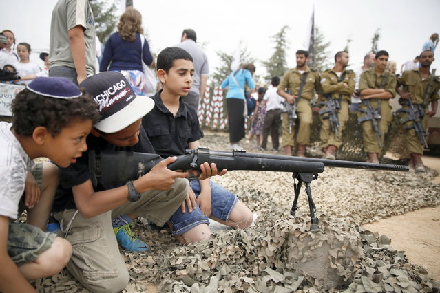 Israeli boys play with a rifle during a traditional military weapon display to mark the 66th anniversary of Israel's Independence at the West Bank settlement of Efrat on May 6, 2014 near the biblical city of Bethlehem. Israelis are marking Independence Day, celebrating the 66th year since the founding of the Jewish State in 1948 according to the Jewish calendar. (Photo by Gali Tibbon/AFP Photo)